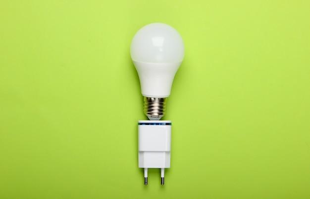 녹색 배경에 충전기와 스마트 에너지 절약 전구. 평면도