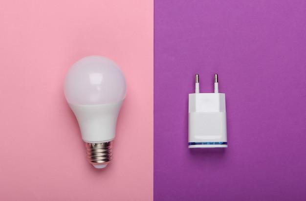 분홍색 보라색 배경에 충전기가있는 스마트 에너지 절약형 전구. 평면도