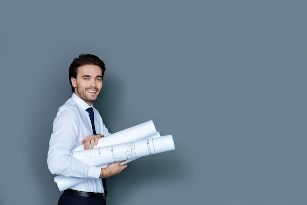 スマートエンジニア。彼の図面を保持し、エンジニアとして働いている間あなたを見ている喜んでハンサムな知的な男