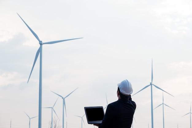 風力タービン分野でコンピューターラボトップを立って使用するスマートエンジニア