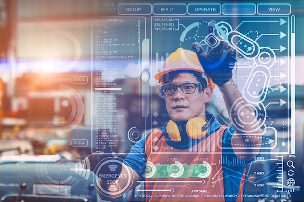 Smart engineer worker using advance technology visual holographic air screen to program and control robotic arm for automated production in modern future factory.