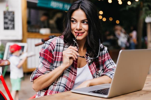 Ragazza europea intelligente che posa scherzosamente con occhiali e laptop. incantevole donna con i capelli neri guardandosi intorno mentre utilizza il computer.