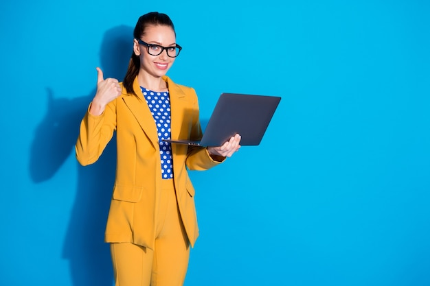 Smart expert ceo worker girl work remote laptop approve business workshop seminar coaching show thumb up sign wear yellow pants trousers jacket blazer isolated blue color background