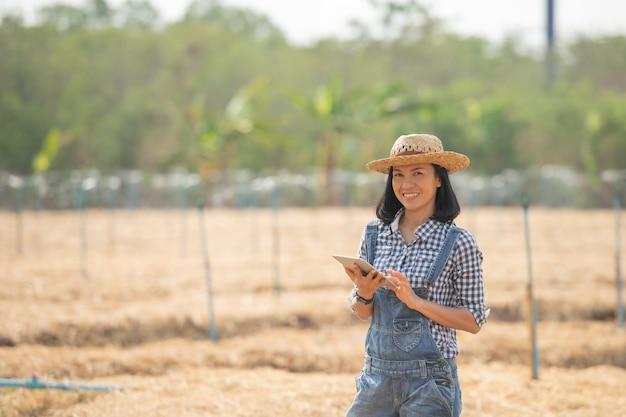스마트 팜. 아름다운 농부는 태블릿을 사용하여 행복과 미소로 농장과 비즈니스를 제어합니다. 비즈니스 및 농업 개념. 농부 또는 농업 경제학자는 채소 재배를위한 음모를 준비합니다.