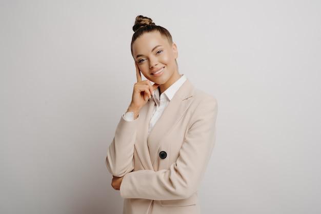 베이지색 정장을 입은 똑똑한 여성 사업가는 재정적 기회를 생각하고 회색 배경에 격리된 단호하고 자신감 있는 자세로 미래 비즈니스 거래를 확보합니다.