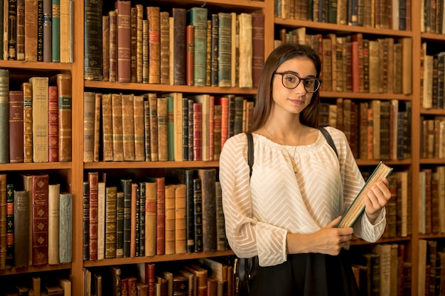 Умная студентка с книгой в библиотеке