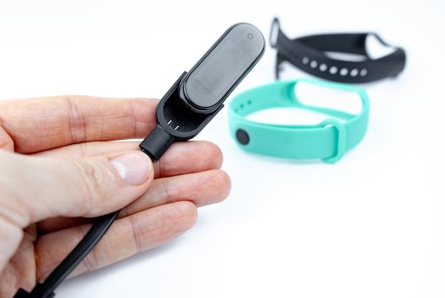 Умный фитнес-браслет с цветным ремешком и зарядным устройством на белом фоне