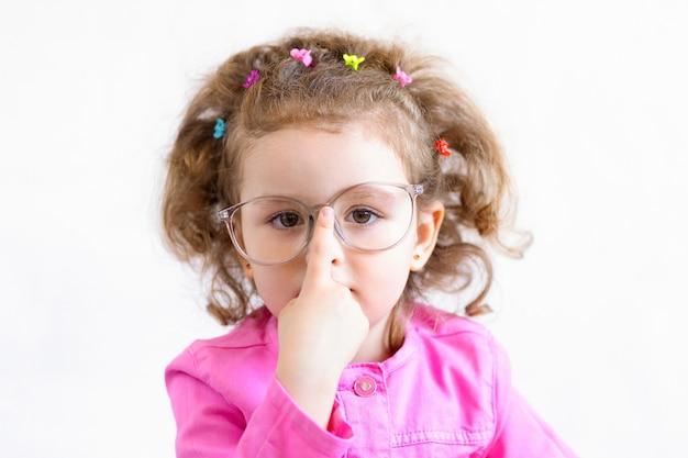 スマートな女の子の大きなメガネ。トレーニング、教育。学校に戻る。鼻の眼鏡を調整する子供