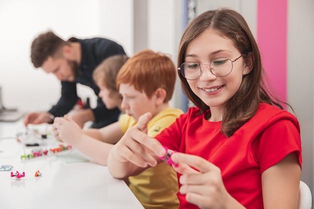 Умная девочка, создающая робота в классе