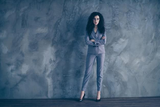 Стенд исполнительного директора умная девушка со скрещенными руками на бетонной стене