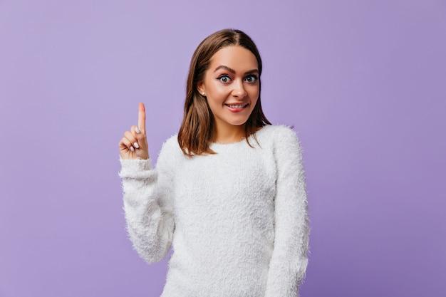 Шикарная девочка 23 лет закусила губу от радости появления новой гениальной идеи. портрет эмоциональной женщины в удобной одежде у фиолетовой стены