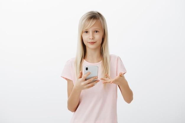 愚かな質問に答えるスマートな女の子。ブロンドの髪を持つ不注意な愛らしい女性の子供の肖像画、手のひらで身振りで示すこと、スマートフォンを保持していることに気づかず、灰色の壁に興味がない