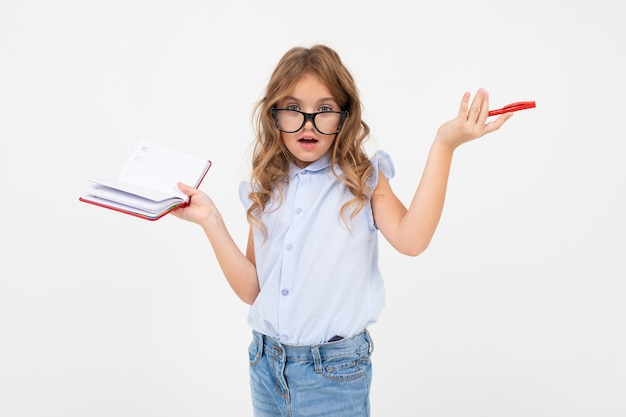 Smart girl with glasses writes a curriculum in a notebook on a white with copy space