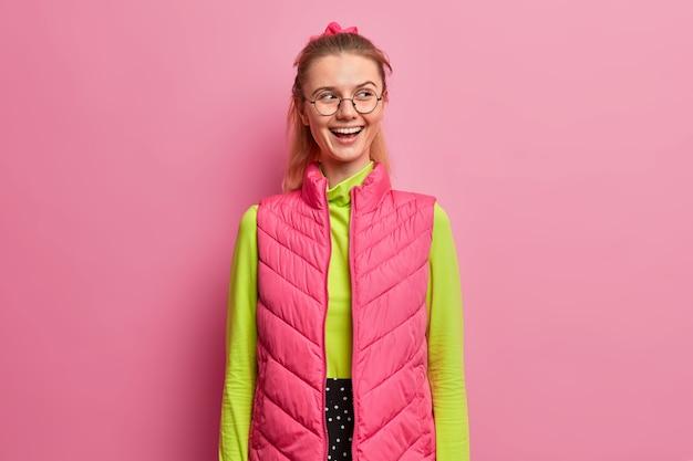Bella ragazza intelligente di ottimo umore, sorride positivamente, guarda da parte, guarda uno spettacolo esilarante, vestita con abiti luminosi, occhiali