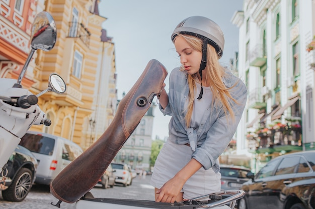 Smart and good-looking woman is looking under motorcycle seat