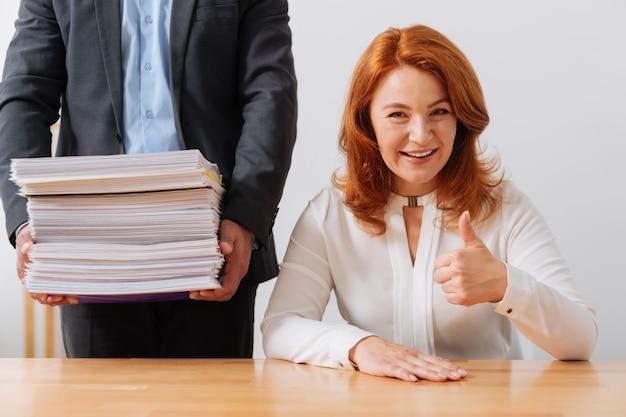 彼女の職場に座って、彼女の考慮のために配達された書類の山を持っているスマートでゴージャスな立派な女性