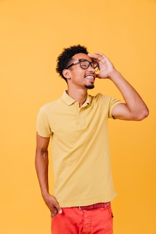 Ragazzo intelligente in abito casual in posa con gli occhi chiusi. foto dell'interno del giovane africano piacevole con gli occhiali.