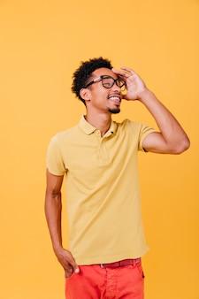 눈을 감고 포즈를 취하는 캐주얼 복장에 똑똑한 사람. 안경에 즐거운 아프리카 젊은 남자의 실내 사진.