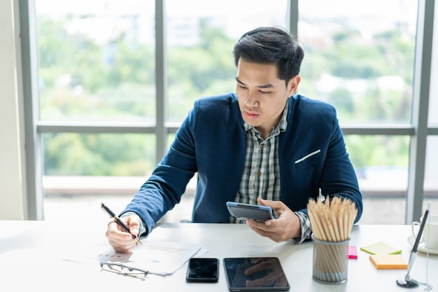 Smart handsome asian businessman working in the office close up.  modern workplace and modern lifestyle .