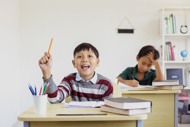 Smart and happy asian elementary  school boy rising his hand in the class