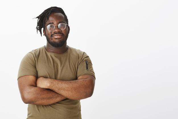 Ragazzo felice intelligente con gli occhiali e indossa una maglietta marrone in posa contro il muro bianco