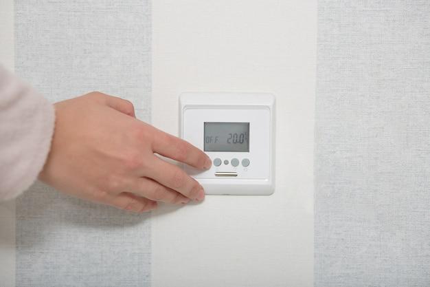 스마트 홈 개념. 흰 벽에 손 puches 버튼 스위치