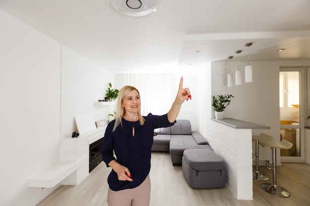 스마트 홈 장치 - 홈 관리. 여자는 가상 버튼을 누른다