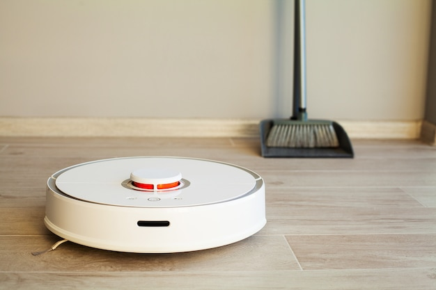 Smart home, robot vacuum cleaner performs automatic cleaning of the apartment at a certain time