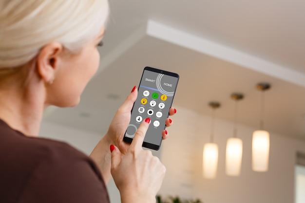 スマートホーム:スマートフォンのアプリで照明を制御する女性
