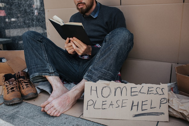 Smart homeless man is sitting on cardboard and reading a book