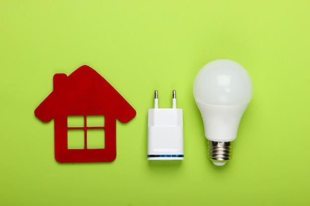 스마트 하우스 개념. 녹색 배경에 충전기와 집과 에너지 절약 전구의 입상. 평면도