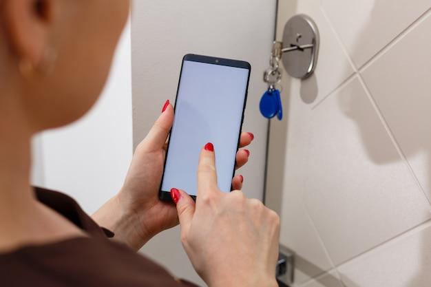 스마트 하우스, 홈 자동화, 앱 아이콘이 있는 장치. 여성은 스마트홈 보안 앱이 있는 스마트폰을 사용하여 집 문을 엽니다.