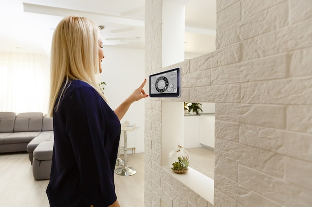 Smart house. nice joyful woman looking at the sensory panel while pressing it