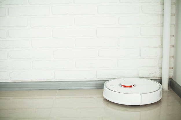 Smart house. vacuum cleaner robot runs on wood floor in a living room.