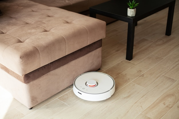 Smart house, vacuum cleaner robot runs on wood floor in a living room,