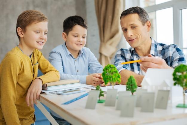 Умные идеи. приятный молодой инженер сидит за столом со своими сыновьями в своем офисе и обсуждает с ними свой проект эко-города во время их визита к нему на работу.
