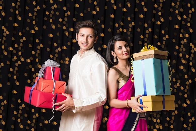 디 왈리 축제 또는 결혼식에 선물 상자와 함께 서있는 스마트 인도 커플