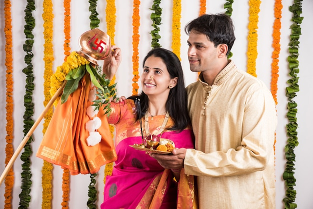 Smart indian young couple performing gudi padwa puja in traditional cloths & pooja thali. it's a hindu new year celebrated across india