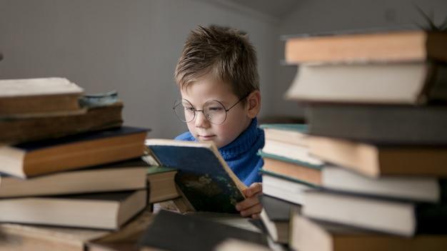 Smart intelligent preschool kid choosing books to borrow.