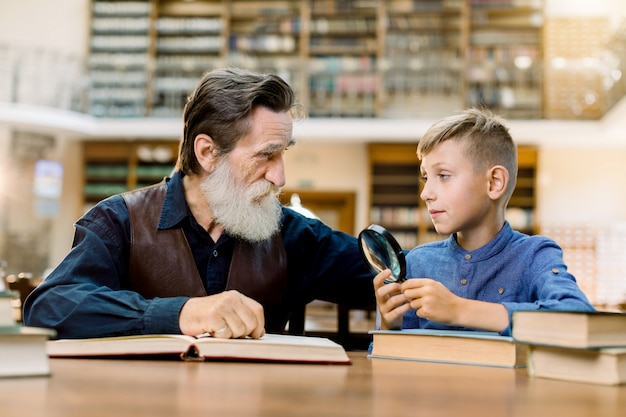 Smart kid boy holds magnifying glass and looking at old man grandfather