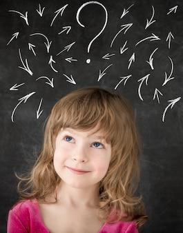 Smart kid in class. happy child against blackboard. drawing arrows. education concept