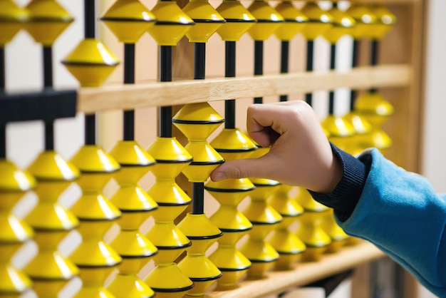 Smart kid counting on soroban abacus. education, school arithmetic, calculating thinking and early development.