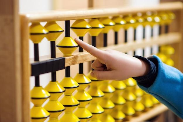 Smart kid counting on soroban abacus