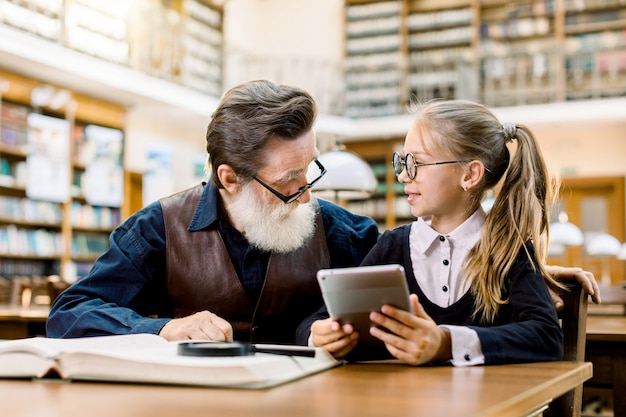 Smart kid girl sitting at the table in old library and holding tablet, showing something on tablet to her teacher or grandfather. senior man with his student little girl in library