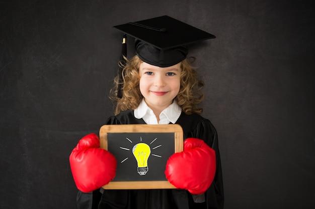 Умный ребенок в классе счастливый ребенок против доски снова в школу образование знания - сила