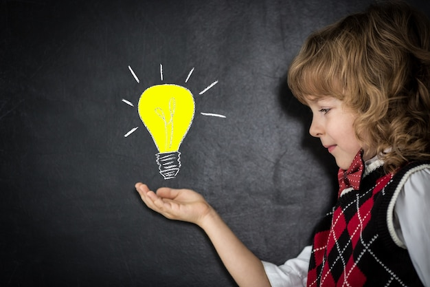 Умный ребенок в классе. счастливый ребенок против доски. яркая идея бизнес-концепции