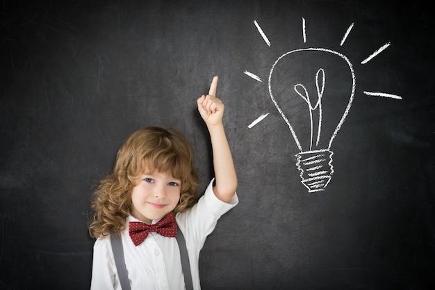 Умный ребенок в классе. счастливый ребенок против доски. рисование лампочки. идея концепции