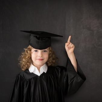 Умный ребенок в классе. счастливый ребенок против доски. идея концепции