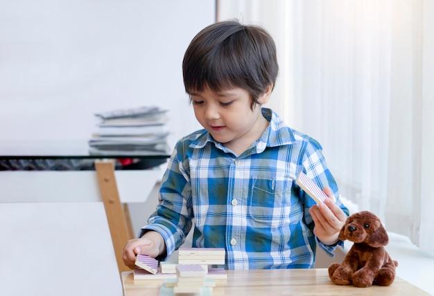 Умный ребенок учится конструированию с деревянными цветными блоками, счастливая детская игра строит игру из деревянных домино, 5-летний мальчик играет в башню из красочных блоков домино