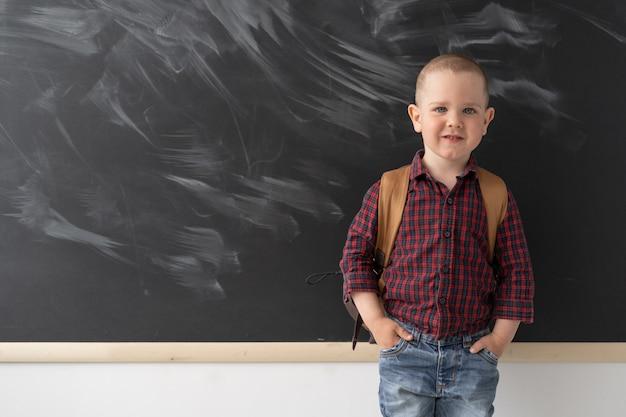 賢い子供男子生徒が黒板の前の教室に立っています。彼はカバンの後ろに暗い格子縞のシャツを着ています。ボードが暗いのでチョークで汚れます。学校に戻る。